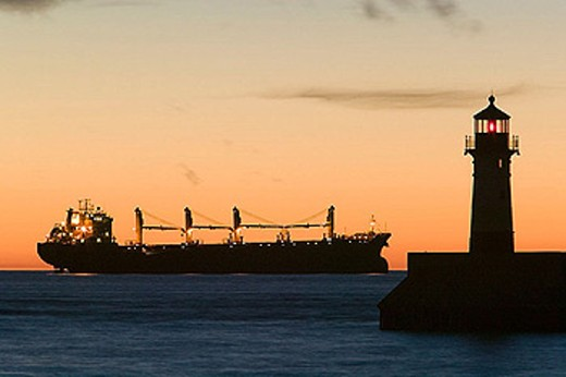 Stock Photo: 1566-324128 Duluth Harbor. Shipping Channel Lighthouse at Dawn with Freighter. Duluth. Minnesota. USA.