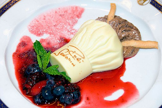 A chefs hat and chocolate mousse with fresh fruit desert on the Holland America cruise ship Zuiderdam. : Stock Photo