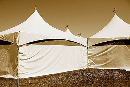 Circus tents with flags flying on top of tents, sepia toned, on grass : Stock Photo