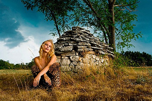 Young woman in front of Istrian ´kazun´ stone hut just before the storm : Stock Photo