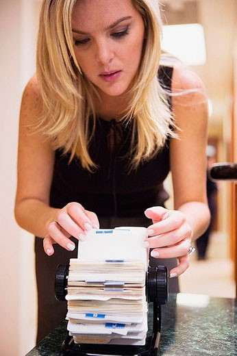 Blonde woman scrolling at business card directory in an office : Stock Photo