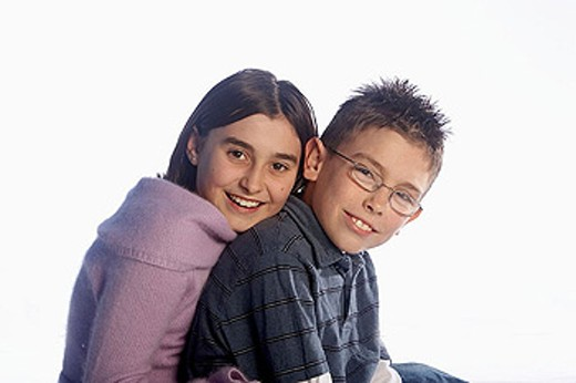 12 year old girl sitting with her 8 year old brother, smiling into camera : Stock Photo