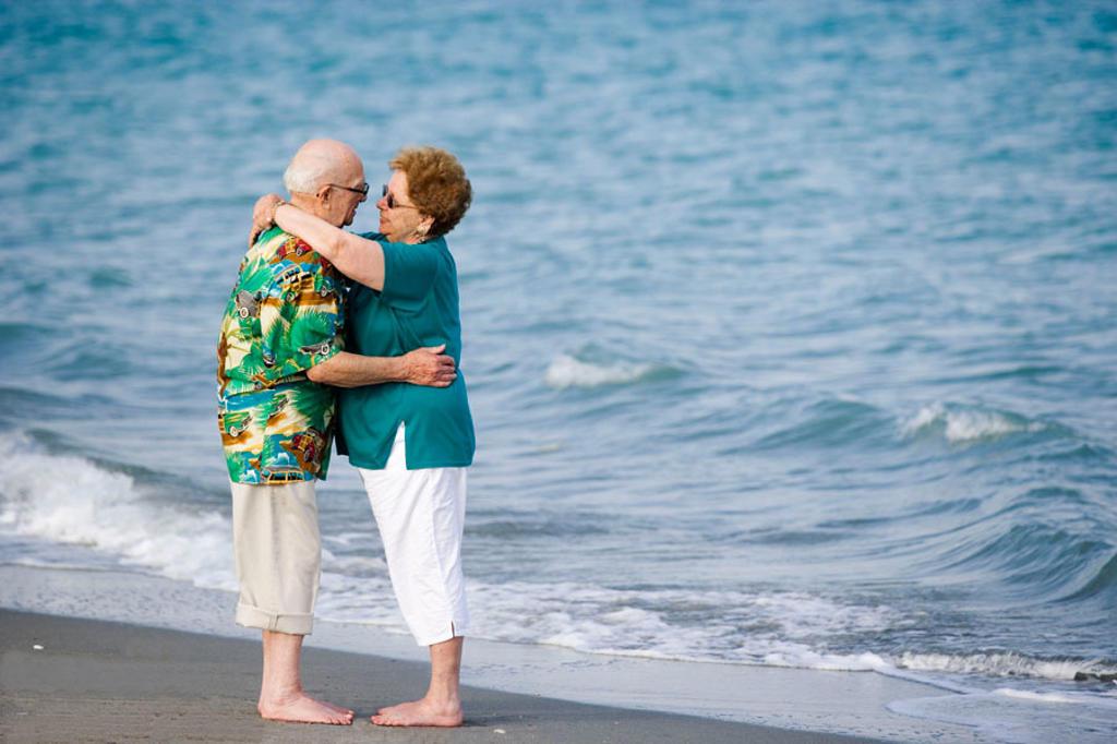 Stock Photo: 1566-338568 Senior couple hugging at the beach