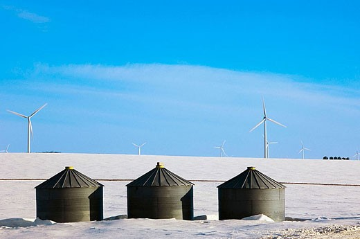 Stock Photo: 1566-338883 Wind Turbines on snowy prairie with graibery buildings. Manitoba, Canada