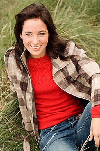 Teen girl sitting in grass : Stock Photo