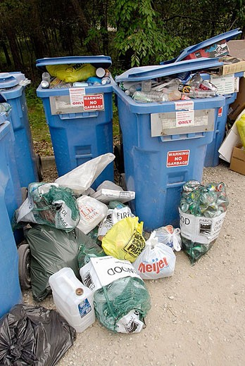 Seperate trash containers are set up in a campgroung to recycle common everyday trash : Stock Photo