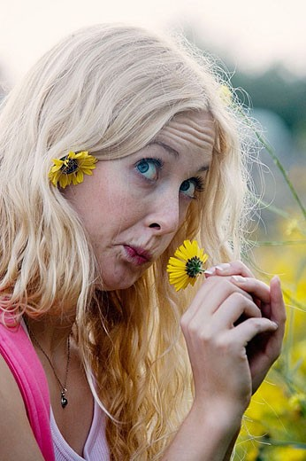 Stock Photo: 1566-348360 Happy silly girl plays with flowers