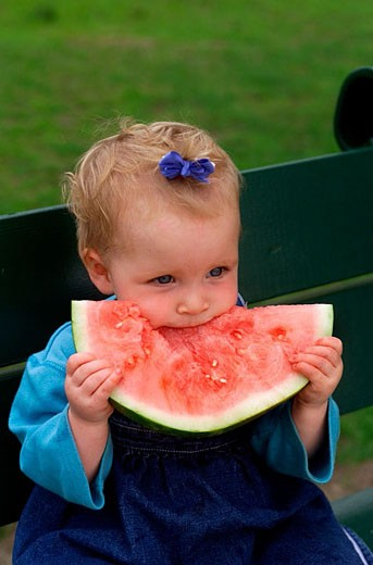 One year old baby girl eating watermelon. : Stock Photo