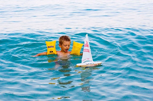 child swimming and plaing with swim arm safe : Stock Photo