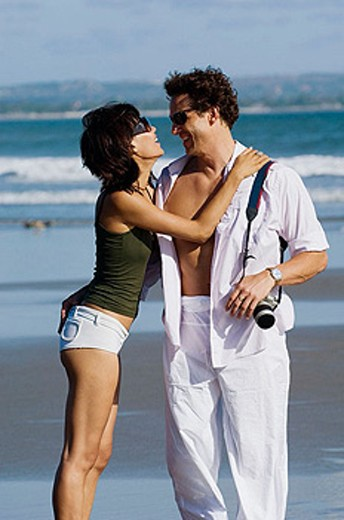 Stock Photo: 1566-355368 couple sightseeing and embracing on beach