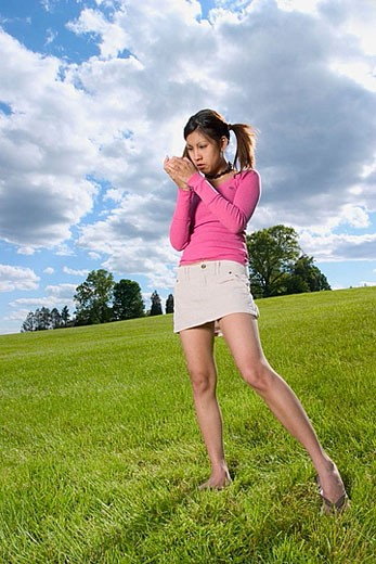 Young Spanish/Asian woman, in pigtails, posing at a park : Stock Photo