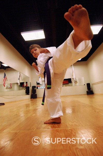 Young boy karate kicking in a karate studio : Stock Photo