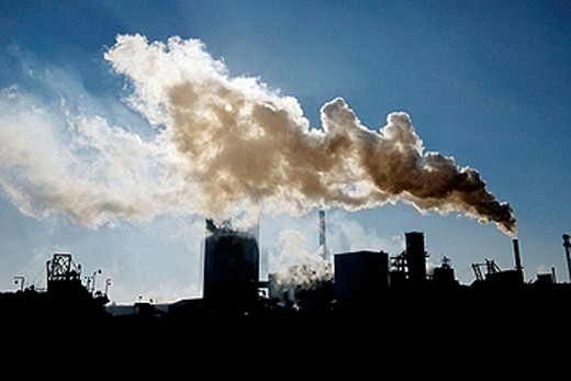 Air pollution pours from smoke stacks from a sugar beet processing plant as a result of burning coal : Stock Photo