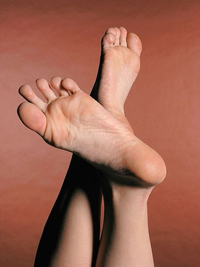 Naked female feet on a brown background : Stock Photo