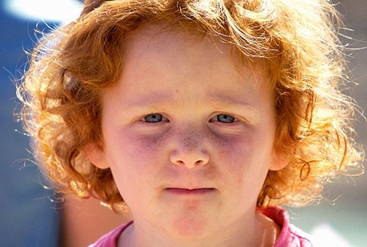 Red Head  with a challenging look, 8 years old. : Stock Photo