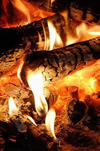 detail of fire in fireplace, glowing coals, yellow-white flames at ends of logs and in embers : Stock Photo