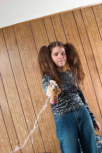 Stock Photo: 1566-369762 Preteen girl, with two large ponytails, squirting liquid string.