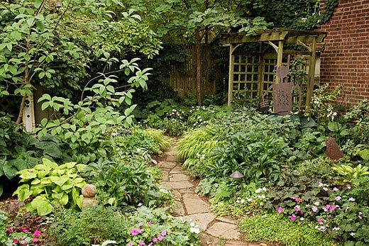 Flagstone path from brick patio leads through shade garden to arbor [Impatiens wallerana; Alchemilla mollis; Hakonechloa macra ´Aureola´; Helleborus x hybridus]. Gross, Wilmington, DE. : Stock Photo