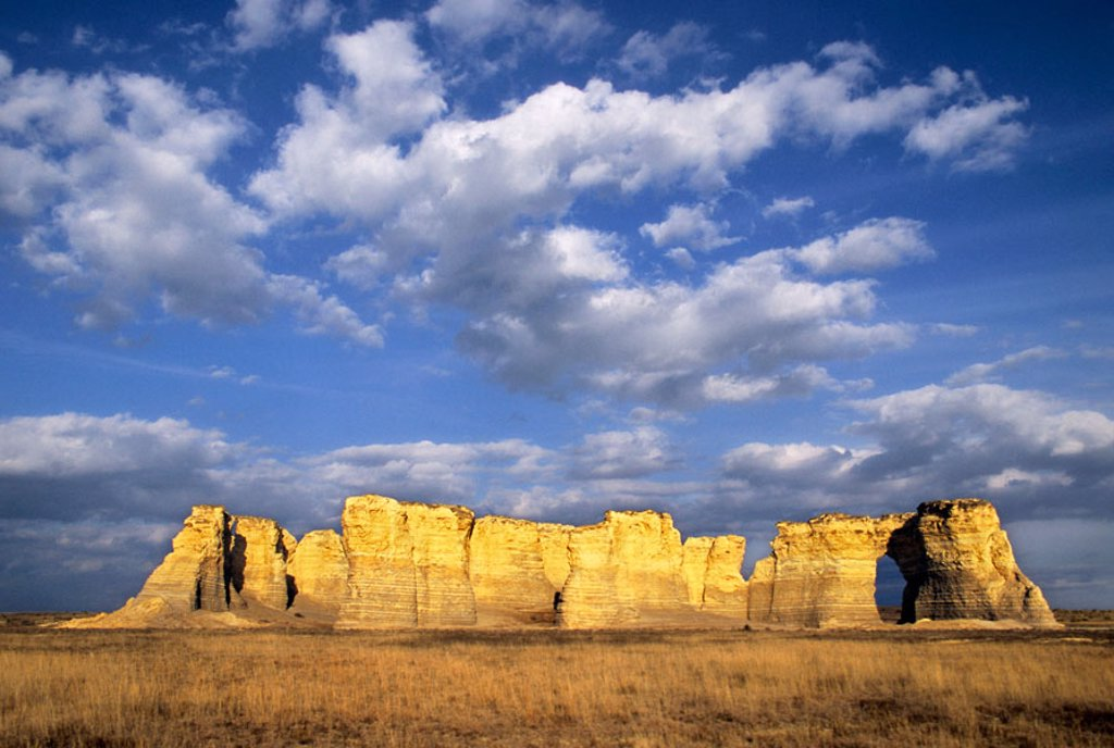 Once buried beneath an ancient sea, Monument Rocks rises from the plains below a sky filled with cottonball clouds, Kansas, USA. : Stock Photo