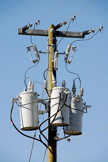 Stock Photo: 1566-376239 Electrical transformers located on poles in a residential neighborhoos
