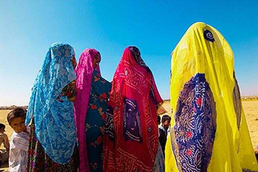 Women in saris watching performances at the Desert Festival, Jaisalmer, Rajasthan, India : Stock Photo