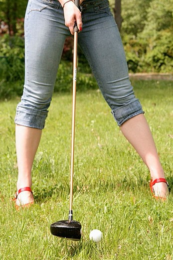 Stock Photo: 1566-380582 Girl with red finger nails and red heels hit golf ball with a driver, funny, humor