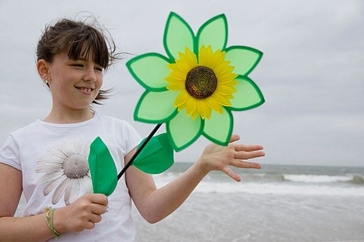 Girl playing with flower-shaped weather vane : Stock Photo