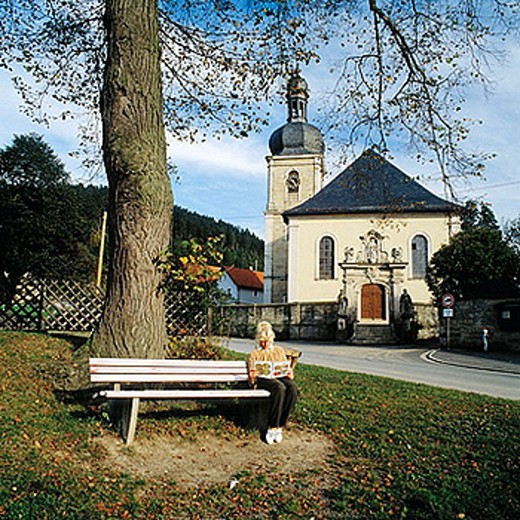 Stock Photo: 1566-384547 Germany, Bavaria, Kronach, Glosberg, parish church and pilgrimage church Saint Mary Glosberg, baroque, young woman sitting on a bench in front of the church reading a book