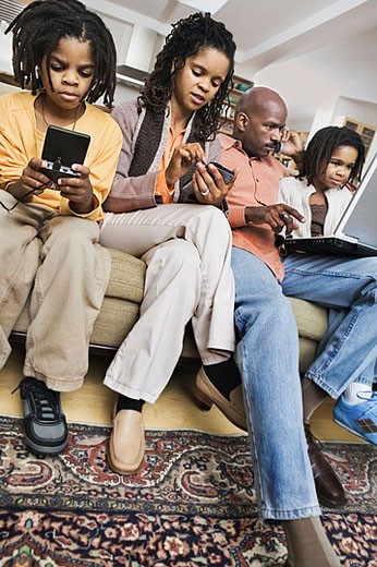 African-American family at home using different technologies including laptop, pda, ipod, cell phone & gameboy. : Stock Photo