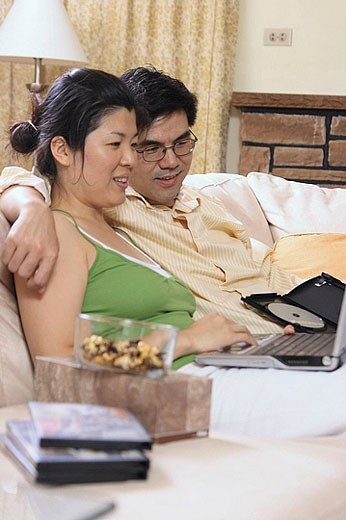 Stock Photo: 1566-387795 Asian couple in their 30´s watching movie on laptop together happily