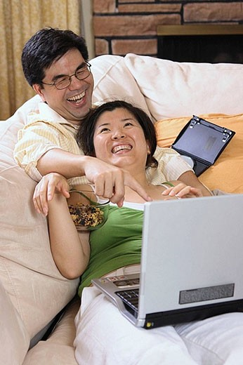 Asian couple in their 30´s watching movie on laptop together having fun : Stock Photo