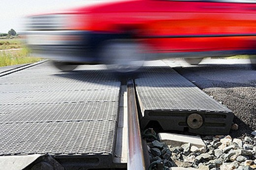 Car crossing rail tracks in a railway crossing without barriers. : Stock Photo