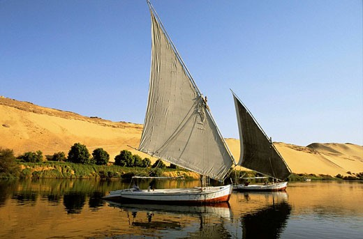 Stock Photo: 1566-396183 Feluccas on the Nile river, in front of the desert western bank,  Aswan, Egypt