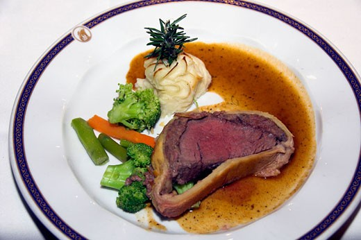 Beef Wellington dinner with vegetables and duchess potatoes on the Holland America cruise ship Ryndam. : Stock Photo