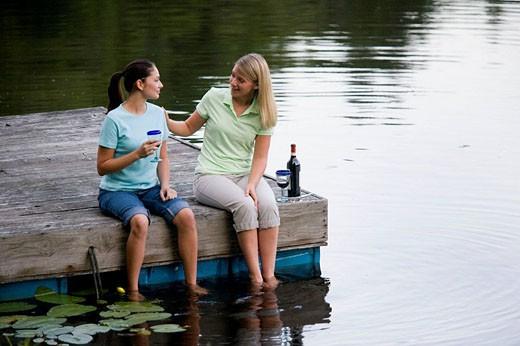 Girlfriends enjoying some wine and conversation on dock : Stock Photo