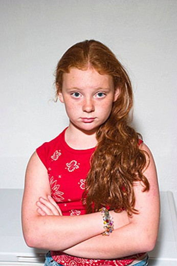 Preteen redhead girl standing in front of a small food freezer, thinking. : Stock Photo