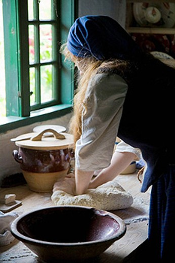 Stock Photo: 1566-405688 Woman in traditional costumes kneading bread. Lejre Forsøgscenter (Open air exhibition). Lejre. Denmark.
