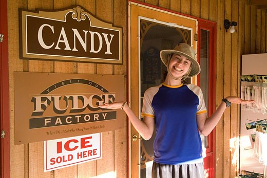 sixteen year old girl smiles outside candy store : Stock Photo