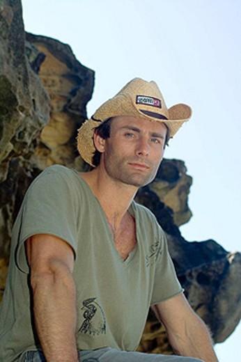 Stock Photo: 1566-411584 Man wearing a cowboy hat, sat on a rock.