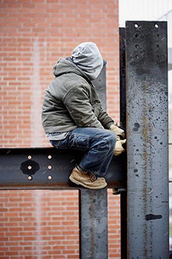Construction iron worker sitting on I beam : Stock Photo