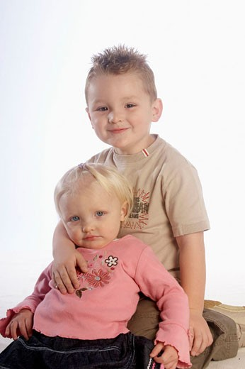 Stock Photo: 1566-420274 2 year old girl sitting with her 4 year old brother, in the studio, smiling into camera