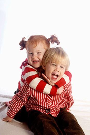 3 year old girl with red hair cuddling her brother ,laughing and smiling into camera, in the studio : Stock Photo