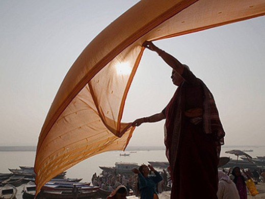 Stock Photo: 1566-420857 A woman dries a wet sari in the early morning sun after bathing in the Ganga river (in accordance with the Hindu belief that such bathing will wash away her sins) in Varanasi, India, a sacred Hindu pilgrimage site.