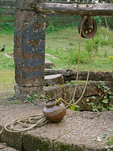 A pot called Ghagar made of copper is joined to ´Rahate´, a pulley used for drawing water out of a well in a traditional way  Velneshwar, Guhagar, Maharashtra, India : Stock Photo