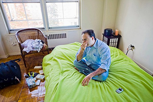 Young man, his cell phone beside him, sitting on his bed in his apartment. : Stock Photo