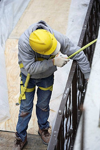 Stock Photo: 1566-429954 Construction worker measuring wall