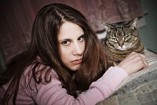 Young woman, with her pet cat, lying on her bed. : Stock Photo