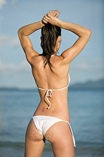 Back view of a brunette woman in bikini looking at the sea : Stock Photo