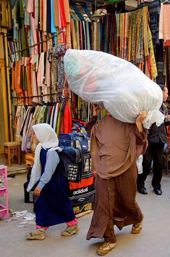A muslim lady carrying a large bundle on her head through the streets of the Khan El Khalili market in Cairo, Egypt : Stock Photo