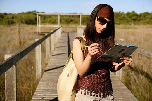 Traveling woman with map in nature landscape : Stock Photo